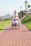 Wife pushing husband on wheelchair Stock Photo