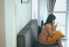 Wife reconcile talking mobilephone to her husband at the living room,Negative attitude emotions. Wife reconcile talking mobilephone to her husband at the living stock photos