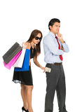 Wife Secretly Inserting Money Husband Pocket. A beautiful shopaholic wife with stylish dress, sunglasses, department store bags secretly inserting saved money Royalty Free Stock Images