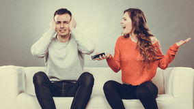 Wife shouting at husband. Cheating man. Betrayal. Angry furious wife shouting at husband showing text messages from lover mistress on his mobile phone. Outraged royalty free stock photo