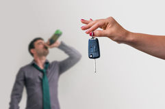 Wife showing car keys and her husband drinking alcohol Stock Images