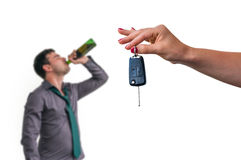 Wife showing car keys and her husband drinking alcohol Royalty Free Stock Image