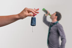 Wife showing car keys and her husband drinking alcohol Royalty Free Stock Photography