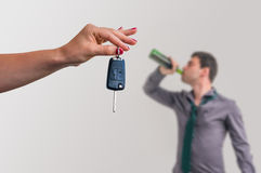 Wife showing car keys and her husband drinking alcohol Royalty Free Stock Photos
