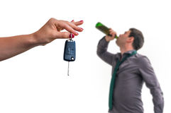 Wife showing car keys and her husband drinking alcohol stock photo
