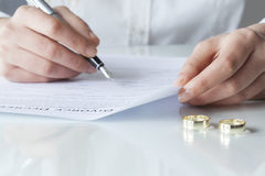 Wife signs divorce decree form with ring Stock Photography
