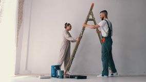 Wife standing on a ladder while her husband paints the wall. And helps her stock video footage
