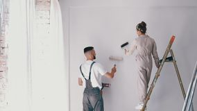 Wife standing on a ladder while her husband paints the wall. And helps her stock footage