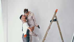 Wife standing on a ladder while her husband paints the wall. And helps her stock video