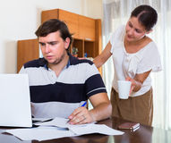Wife taking care of working husband Stock Photo