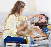 Wife taking care of young husband with flue at home Stock Photography