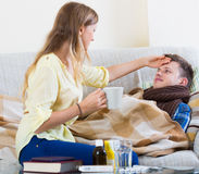 Wife taking care of young husband with flue at home Royalty Free Stock Photography