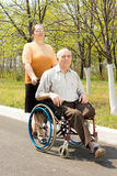 Wife taking her disabled husband for a walk Stock Photo
