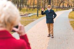 wife taking photo of her senior husband waving stock photography