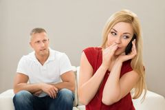 Wife talking on mobile phone while husband on sofa. Wife Talking Privately On Mobile Phone While Husband Sitting On Sofa Royalty Free Stock Images