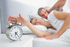 Wife turning off alarm clock as husband is covering ears Royalty Free Stock Photos