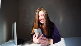 Wife using phone, texting husband and receives letters. Young woman holds in hands smartphone. Smiling and happy wife receives husband s letters from Europe stock footage