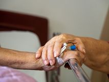 Wife visiting husband in hospital. Senior couple holding hands on hospital bed for hospitalization for supporting his dear. Concep stock images