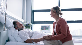 Wife visiting husband in hospital. Woman consoling hospitalised man Stock Image