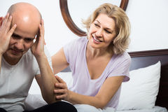 Wife warmly comforting upset husband in bedroom Stock Images