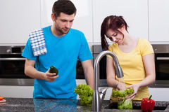 Wife washing broccoli in kitchen Stock Photography