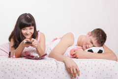 Wife watching comedy on TV, my husband sleeps Royalty Free Stock Photo
