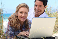Wife working on laptop on the beach. Royalty Free Stock Images