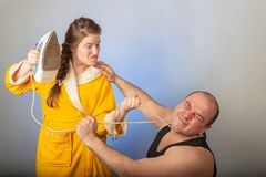 A wife in a yellow robe beats a bald husband, the concept of a family quarrel royalty free stock images