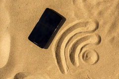 在海滩的手机和WiFi签字 免版税库存照片