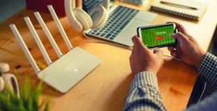 Wifi di collegamento del router del giovane sullo smartphone per Internet ed il flusso continuo online Live immagine stock