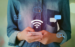 Wifi and digital network data icon over hand using smart phone b Royalty Free Stock Images