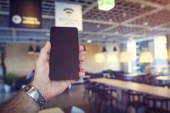 Wifi fri zon Den svarta moderna smartphonen mans in handen mot kafébakgrund zon Wi-fi i kafé Wi fi frigör i restaurang Royaltyfri Fotografi