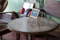 Wifi sign on wood table in public cafe. Natural light. Royalty Free Stock Images
