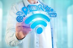 Wifi symbol connection surrounded by multimedia and internet app. View of a wifi symbol connection surrounded by multimedia and internet application logo - 3d Royalty Free Stock Image