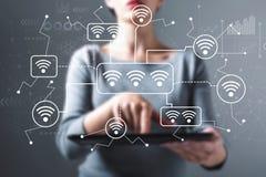 WiFi tema med kvinnan som anv?nder en minnestavla arkivbilder