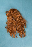 Wig on carpet. A wig thrown on the floor, on a turquoise carpet Royalty Free Stock Photos