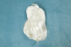 Wig on carpet. A wig thrown on the floor, on a turquoise carpet Royalty Free Stock Photo