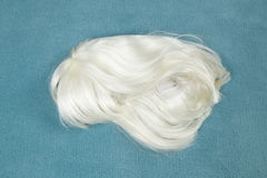 Wig on carpet. A wig thrown on the floor, on a turquoise carpet Stock Image