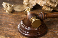 Wig and gavel. Wooden block, judge's wig and gavel on a wooden desk royalty free stock photos