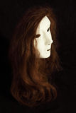 Wig on mask. Brown wig on white mask, with black background Royalty Free Stock Photo