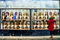 The wig shop. Street photo style photo of a young woman looking at a weathered wig shop with lots of mannequin heads on display wearing different artificial hair