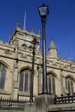 Wigan parish church. With 2 old style lampposts and wrought iron fence in foreground Stock Photo