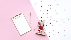 Wooden christmas deer and note on pink and white background. Copy space stock image