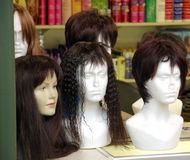 Wigs in Display. A number of damaged mannequin heads displaying wigs on a shop display counter Stock Photography