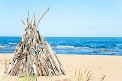 Wigwam Made from wooden branches on the sand of baltic sea beach royalty free stock photography