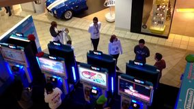 Wii staff demonstrates with people playing car racing game. Inside mall stock footage