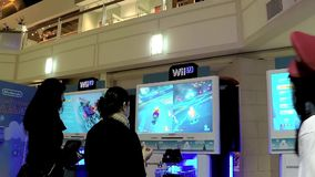 Wii staff demonstrates with people playing car racing game. With wide angle shot stock video footage