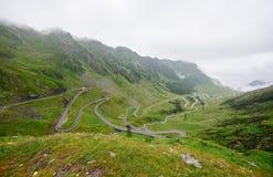 Wijąca ścieżka w zielonych skalistych górach i trawiastych łąkach Zdjęcie Royalty Free