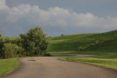 Wijąca droga przez trawiastych wzgórzy Fotografia Stock