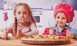 Wij houden van pizza! De leuke beste vrienden die van weinig kindmeisjes pizza eten stock foto's